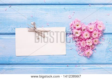 Background with heart from pink flowers and petals and empty tag on blue wooden planks. Selective focus. Place for text.