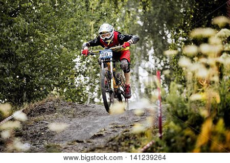 Magnitogorsk Russia - July 23 2016: male extreme racer on bike rides over rocks in forest during National championship downhill