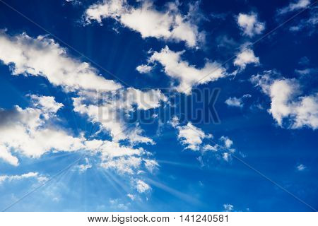 Blue sky with white clouds through which the sun is shining with visable sun beams