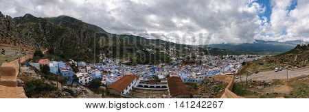 An awesome panoramic view over the blue painted and famous city Chefchaouen in Morocco. It is located in the Rif Mountains. The sky is cloudy.