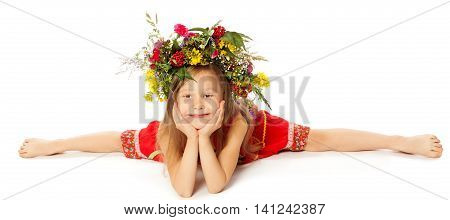 Adorable little girl in a bright red dress with a large floral wreath on his head. Girl does the splits-Isolated on white background