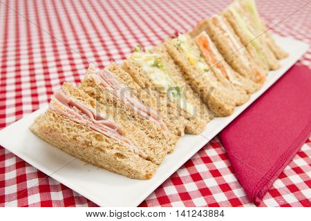Sandwiches with various fillings A white plate of different triangular sandwiches