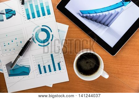 Business Desk with Digital Tablet, Coffee, Eyeglasses and Business Graphs