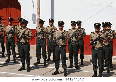 Magdalena, Cajamarca, Peru - July 25, 2016: Three rows of policemen stand with machine guns in street in Magdalena, Cajamarca, Peru on July 25, 2016