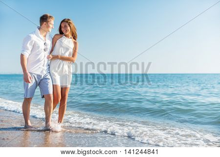 Beach couple walking on romantic travel honeymoon vacation summer holidays romance. Young happy lovers, Asian woman and Caucasian man holding hands embracing outdoors