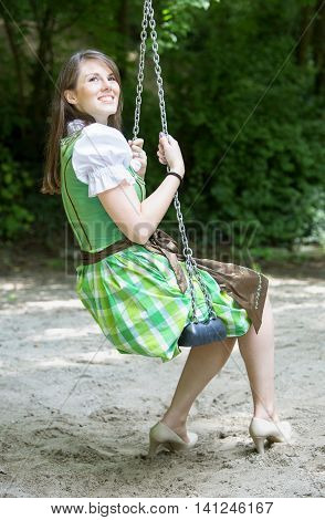 bavarian woman in dirndl sitting on swing outdoors