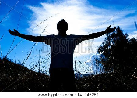 Man praying meditating in harmony and peace at sunset. Religion spirituality prayer peace.