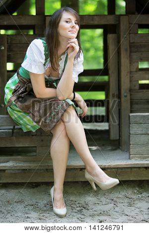 young woman wearing a dirndl sitting at wooden lodge
