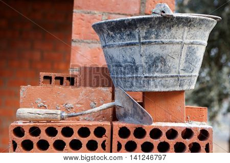 Bricks stacked trowel and cube in the work. Construction materials