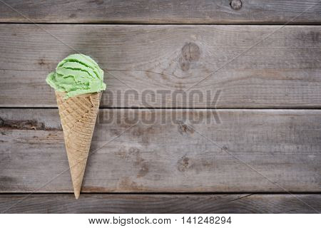 Top view single scoop green tea ice cream in a waffle cone over old rustic wooden background with copy space.