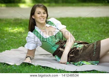 young bavarian woman in dirndl lying on blanket in park