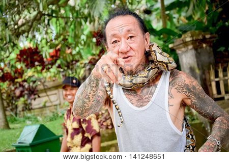 Bali Indonesia - August 11: Balinese man and the snake show for traveler and tourism can take photo with him or his snake. on August 112011 at Temple in Bali Indonesia.