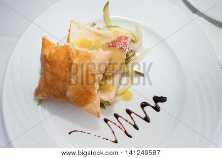 Baked red mullet in puff pastry on white plate