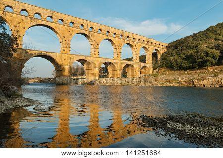 Famous Pont Du Gard reflecting in Gardon river in Southern France