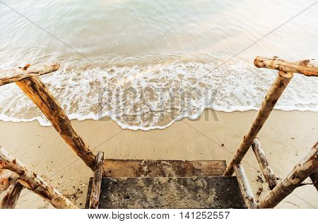 Wooden railing with sand beach and motion blur of the water on the sea in morning light