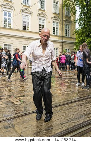 Lviv Ukraine - May 2 2016: Celebration pouring water on Monday after Easter by the town hall. Bald man dancing among a people.