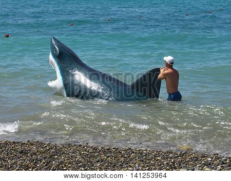 Sochi Russia - June 30 2014: Man walks with a hoax sharks in the water along the beach in Sochi