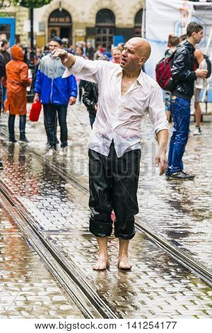 Lviv Ukraine - May 2 2016: Celebration pouring water on Monday after Easter by the town hall. Bald men dancing among a people