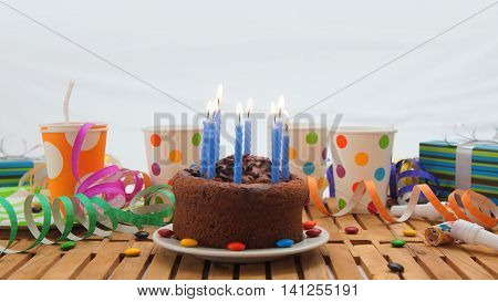 Chocolate birthday cake with a blue candles burning on rustic wooden table with background of colorful streamers, gifts, plastic cups with candies and white wall in the background