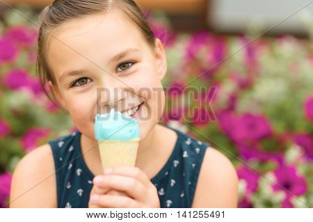 Little girl is eating ice-cream in park, outdoor shoot