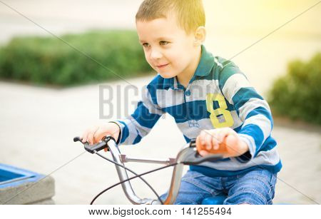 Cute boy is riding bicycle, outdoor portrait