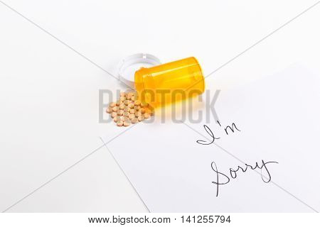 Pills spilling out of medicine bottle with I'm Sorry note, implication suicide overdose