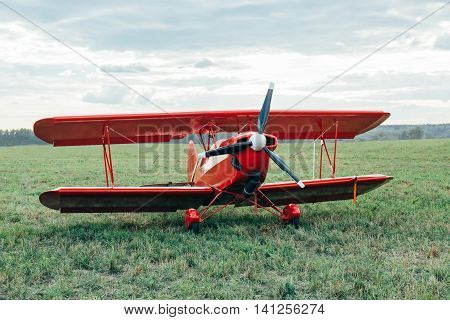 Red biplane without a pilot standing in a field.