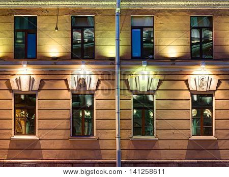 Several windows in a row on night illuminated facade of urban apartment building front view St. Petersburg Russia