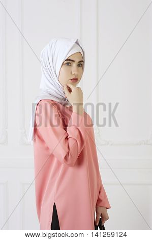 studio portrait of a beautiful young Caucasian woman in a modern closed east clothes and a scarf on her head tatarstan