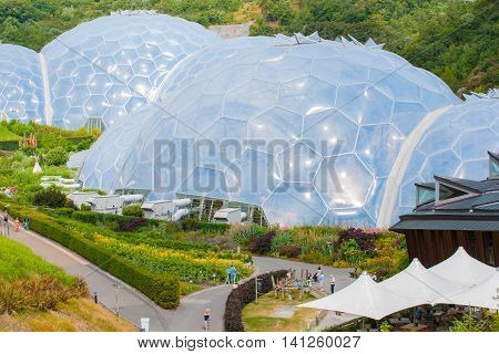 Cornwall, England - July 24, 2013: Eden Project white geodesic biome domes surrounded by outdoor gardens is tourist attraction and plant research and environmental education complex on Cornwall England.