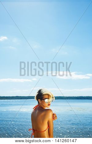 High fashion look.glamor beautiful sexy stylish blond Caucasian young woman model with bright makeup and sunglasses with perfect sunbathed clean skin in swimsuit on beach