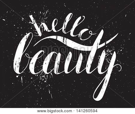 Grunge handwritten calligraphic ink inscription Hello beauty on black background with splatters. Hand write lettering for poster, postcard, t-shirt, greeting card, invitation. Vector illustration.