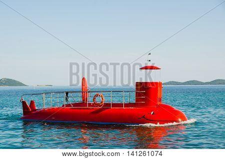Red tourist semi-submarine at sea without capitan. Blue mediterranean sea in Croatia. Funny submarin no people at board.
