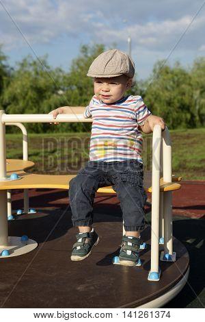 Child Sitting On Roundabout