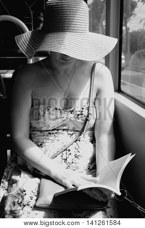 Woman in b/w image, reading a book on train bus.