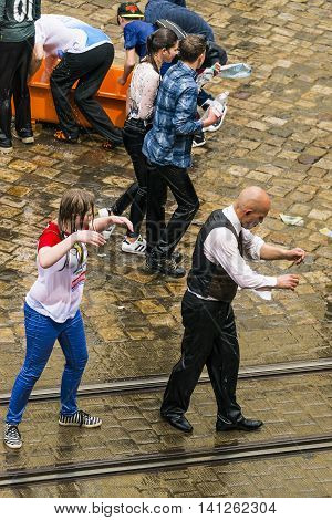 Lviv Ukraine - May 2 2016: Celebration pouring water on Monday after Easter by the town hall. Bald men danc with wet girl