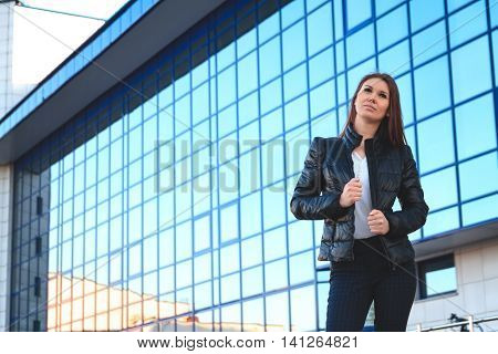 Portrait of a beautiful young lady in beznes informal dress on a background of the business center. The informal business, free business concept
