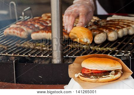 Grill sausage and burgers on a grill pan, barbecue party at the summer picnic outdoors