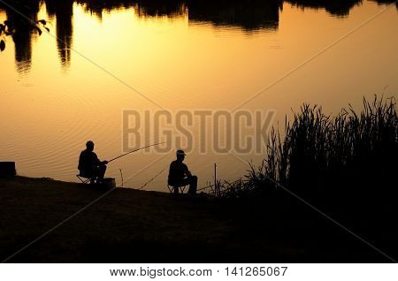 silhouettes of two fishermen on sunset background