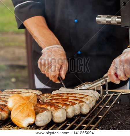 Close-up of a hands man, dressed in a black shirt, cooking spicy browned sausages on the hot grill . Grill concept