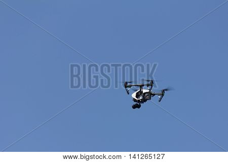 flying a quadcopter is videotaping against the clear blue sky