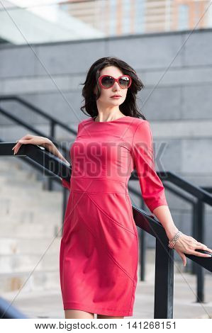 Alluring Lady In Red Dress And Sunglasses Posing Near The Stairs Outdoors