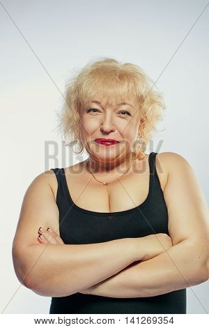 Pretty beautiful mature lady in black dress posing over white background