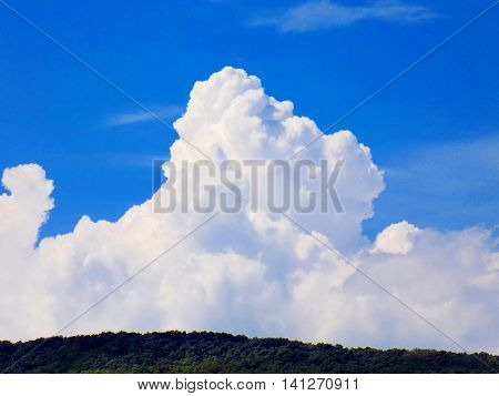 Cumulonimbus convective cloud indicating storm formation through low pressure system in unstable atmosphere during summer