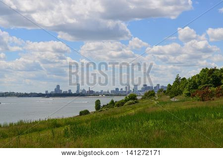 Cityscape of Boston with puffy white clouds over Boston from the harbor.
