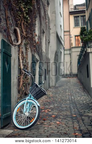 Ladies Bicycle With Basket Parked On The Street On Old European Town;