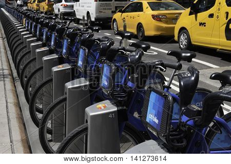 New York NY USA -- Aug 3 2016 A row of Citibikes parked along 43rd Street with crosstown traffic in the background. Editorial Use Only.