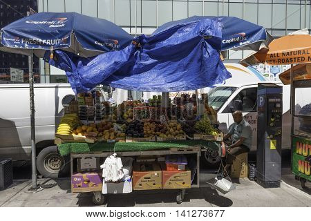 New York NY USA -- Aug 3 2016 A street vendor sits by his fruit cart in Midtown amid heavy traffic. Editorial Use Only.