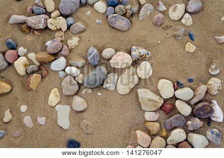 Beautiful sand background with pebbles. Close up view beach sand background. Sandy texture with stones. Brown sand. Background from fine sand. Summer concept. Top view.