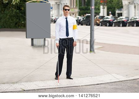 Blind Man Wearing Armband Standing On Sidewalk